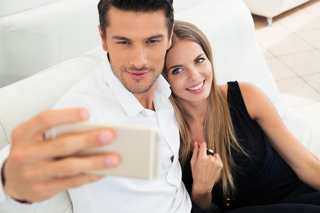 Smiling young couple making selfie photo on smartphone indoors