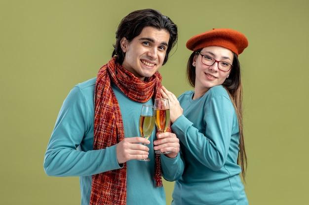 オリーブグリーンの背景で隔離のシャンパングラスを保持している帽子をかぶってスカーフの女の子を着てバレンタインデーの男に笑顔の若いカップル
