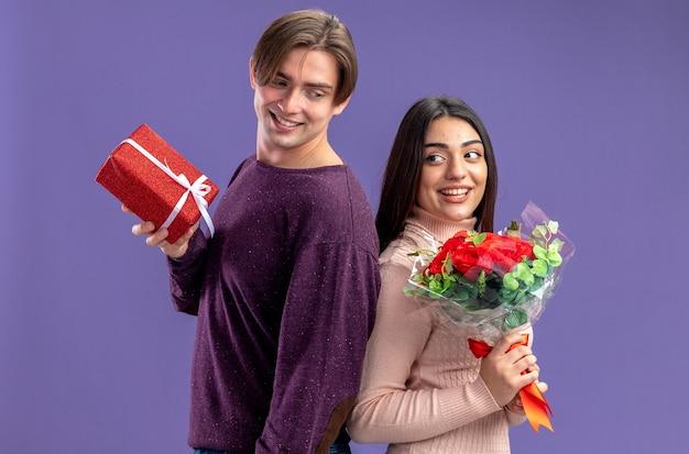 青い背景で隔離のギフトボックスと花束と背中合わせに保持しているバレンタインデーに若いカップルの笑顔