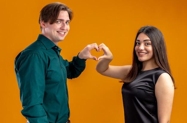 オレンジ色の背景で隔離の心のジェスチャーを示すバレンタインデーに若いカップルの笑顔