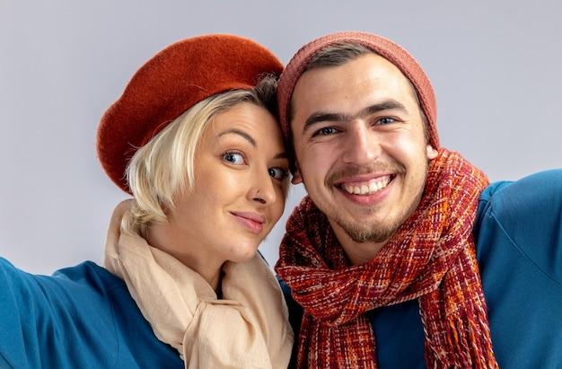 白い背景で隔離のカメラを保持しているスカーフと帽子をかぶってバレンタインデーに若いカップルの笑顔