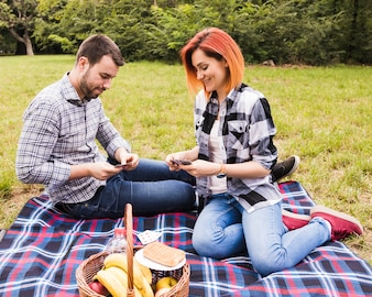 Smiling young couple playing cards on picnic in the park