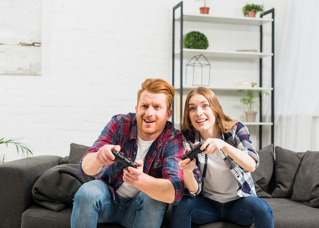 Smiling young couple playing the video game with joystick