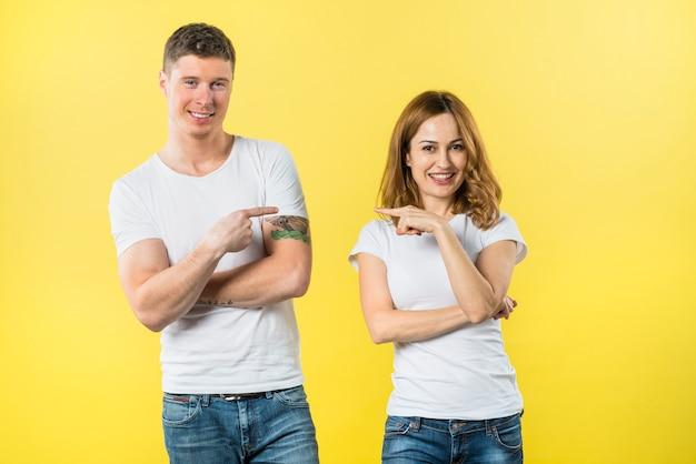 Smiling young couple pointing fingers to each other looking to camera