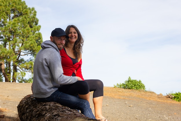 Smiling young couple posing sitting on tree trunk at forest on sunny day. man on hood and cap and woman resting happily on hiking trek