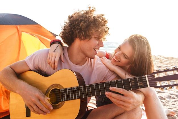 Улыбающаяся молодая пара отдыхает вместе на пляже, в кемпинге, играет на гитаре