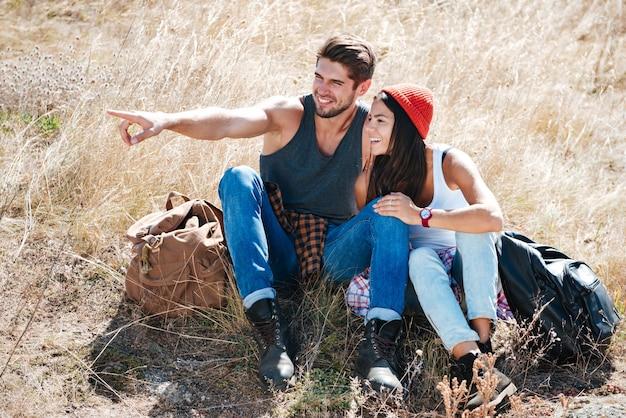 Улыбающаяся молодая пара, отдыхая вместе на открытом воздухе и указывая пальцем
