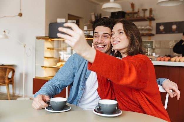 一緒にカフェのテーブルに座っている若いカップルの笑顔