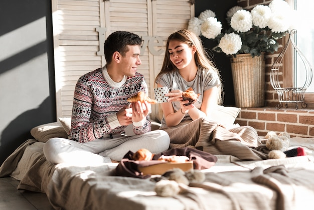 Smiling young couple sitting on bed holding croissant and cupcake in hand