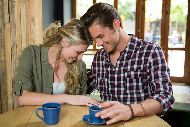 コーヒーショップのテーブルに向かい合って座っている若いカップルの笑顔