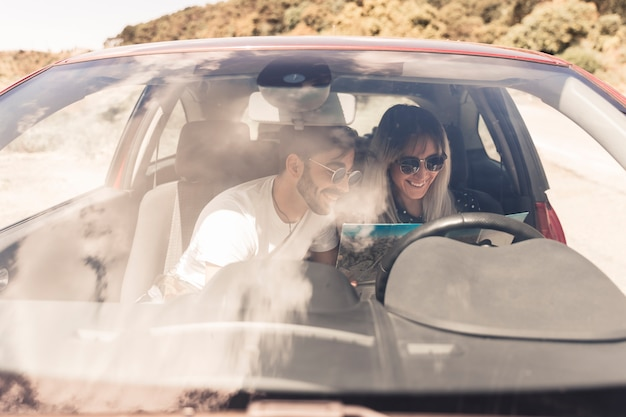 Smiling young couple sitting inside the car looking at map