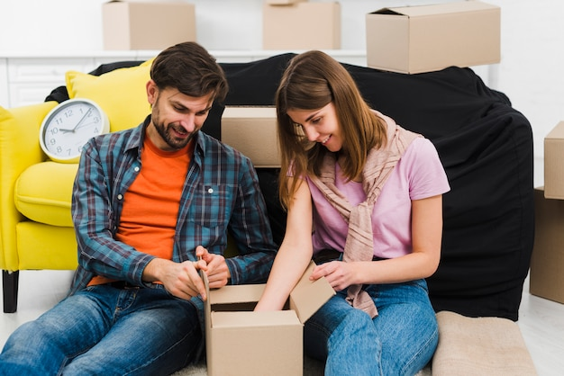 Smiling young couple sitting near the sofa unpacking the box in new house