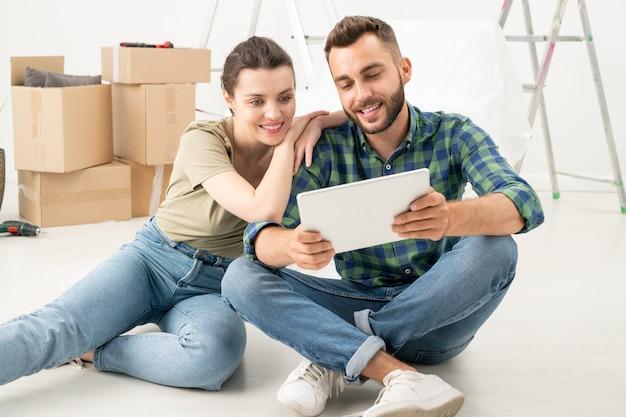 新しいアパートの床に座って、タブレットを使用してオンラインで家具を注文する若いカップルの笑顔