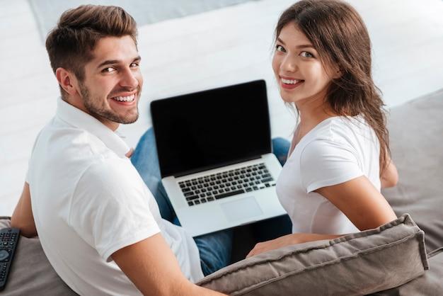 ソファに座って、空白の画面のラップトップを使用して笑顔の若いカップル