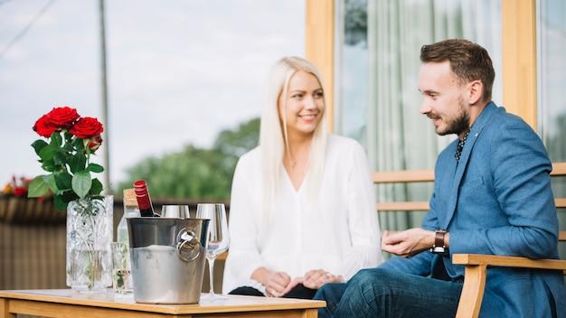 テーブルに氷のバケツと一緒に座っている若いカップルに笑顔