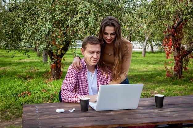 笑顔の若いカップルは、ラップトップを持って木製のテーブルに座って、公園で一緒に時間を過ごし、勉強し、仕事をしています。公園でガジェットを持つ女の子と男