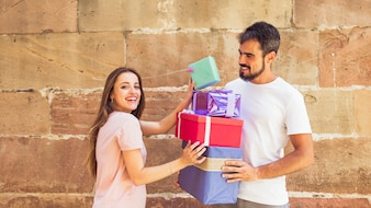 Smiling young couple stacking gifts in front of weathered wall