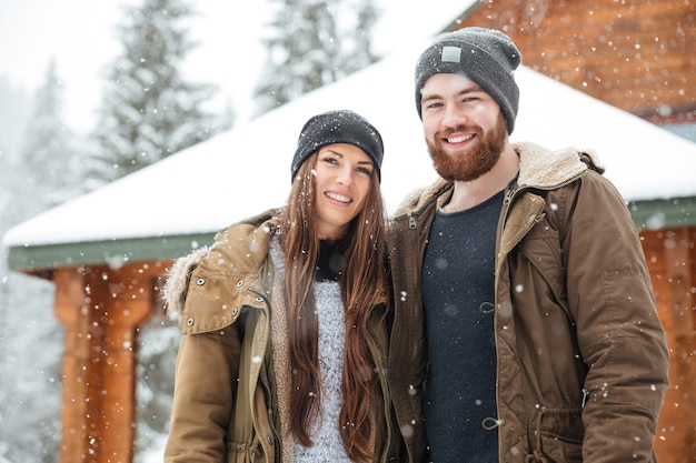 Smiling young couple standing in front of log cabine in winter mountains