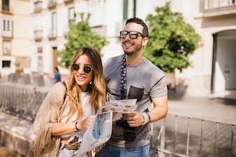 Smiling young couple standing on street holding map