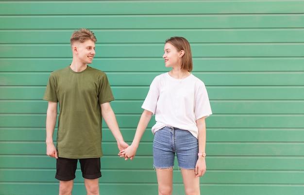 Улыбающаяся молодая пара, стоящая на зеленой стене