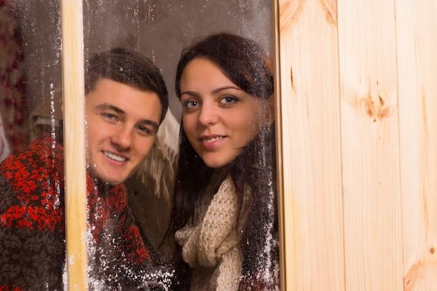 冬の冷ややかな窓ガラス越しに並んで立って、笑顔でカメラを見て笑顔の若いカップル