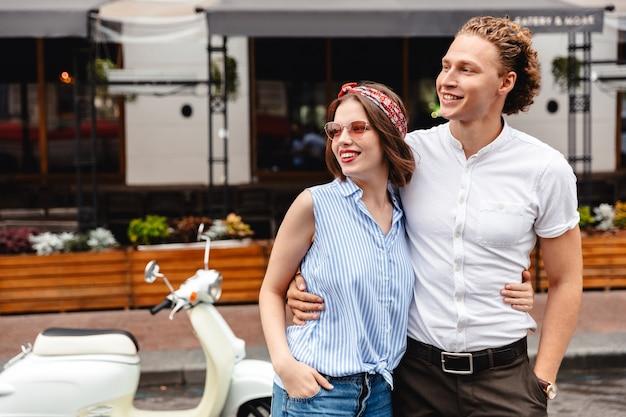 Улыбающаяся молодая пара, стоящая вместе с мотоциклом на городской улице