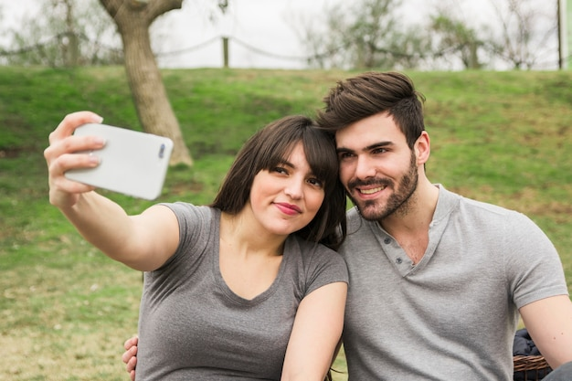 Smiling young couple taking self portrait on cell phone in the park