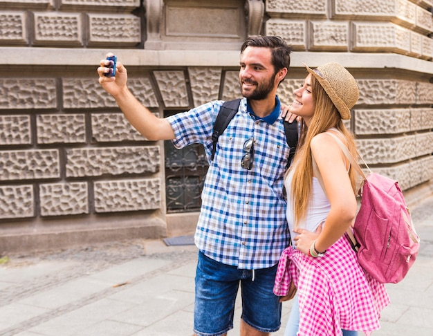 Smiling young couple taking selfie on mobile phone