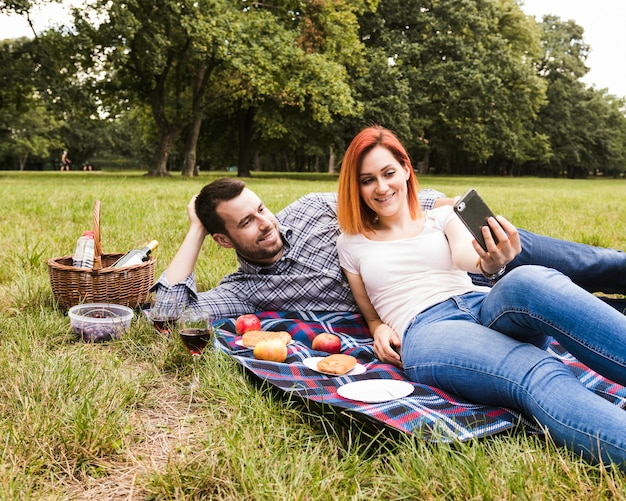 Smiling young couple taking selfie in the picnic