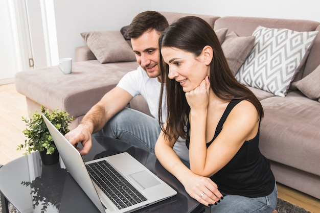 Smiling young couple using laptop at home