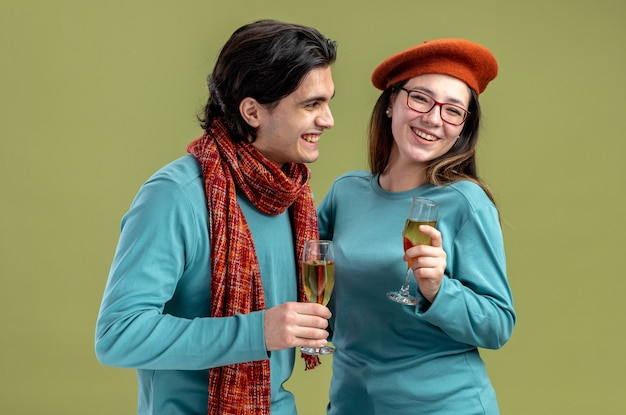 Smiling young couple on valentines day guy wearing scarf girl wearing hat holding glass of champagne isolated on olive green background