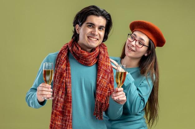 Sorridente giovane coppia il giorno di san valentino ragazzo che indossa una sciarpa ragazza che indossa un cappello con in mano un bicchiere di champagne isolato su sfondo verde oliva