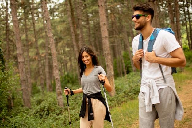 여름 날 숲에서 배낭과 함께 산책하는 젊은 부부 미소