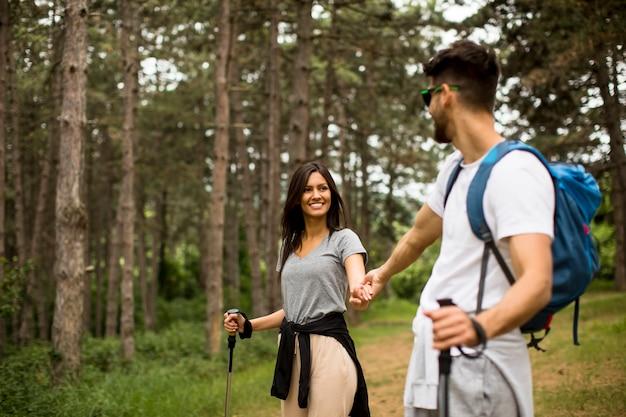 숲에서 배낭을 함께 걷는 젊은 부부 미소