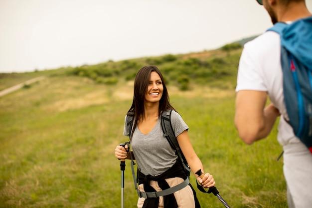 여름 날에 푸른 언덕에 배낭과 함께 걷는 젊은 부부 미소