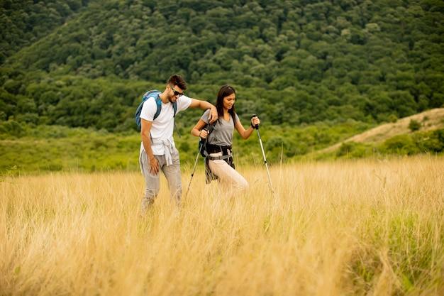 Улыбающаяся молодая пара гуляет с рюкзаками по зеленым холмам