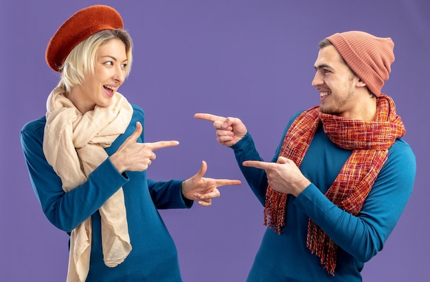 バレンタインの日に帽子をかぶって笑顔の若いカップルが青い背景で隔離されたお互いを指しています