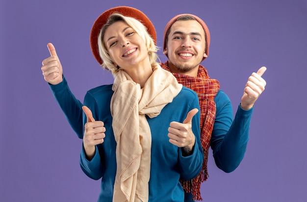 Улыбающаяся молодая пара в шляпе с шарфом в день святого валентина показывает палец вверх, изолированные на синем фоне
