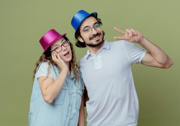 ピンクと青の帽子の女の子が頬に手を置いて、オリーブグリーンで隔離の平和のジェスチャーを示す男を着て笑顔の若いカップル