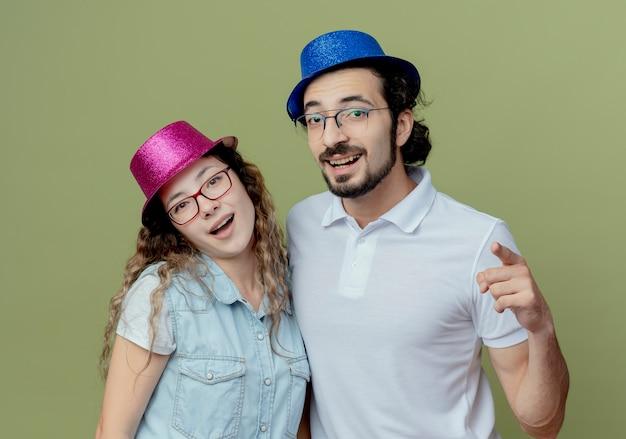올리브 그린에 고립 된 제스처를 보여주는 분홍색과 파란색 모자 남자를 입고 젊은 부부 미소