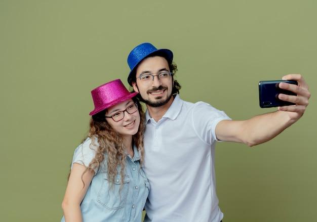 분홍색과 파란색 모자를 쓰고 웃는 젊은 부부는 올리브 그린에 고립 된 셀카를 가지고