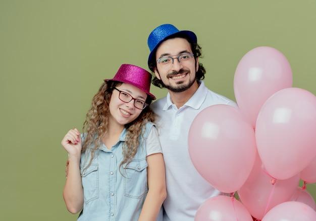Sorridente giovane coppia indossando cappello rosa e blu in piedi palloncini vicini isolati su verde oliva