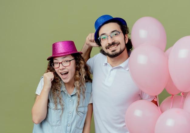 Sorridente giovane coppia indossando cappello rosa e blu in piedi palloncini vicini e mostrando sì gesto isolato su verde oliva