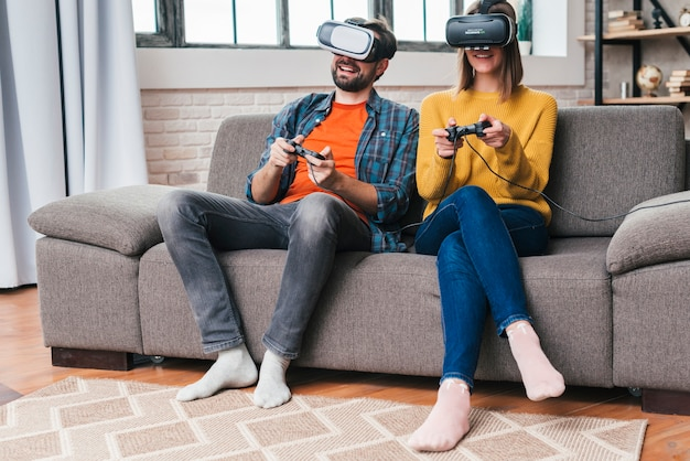 Smiling young couple wearing the virtual reality glasses playing the video game