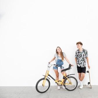 Улыбаясь молодая пара с велосипедом и скейтборд против стены