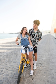 Smiling young couple with bicycle at port