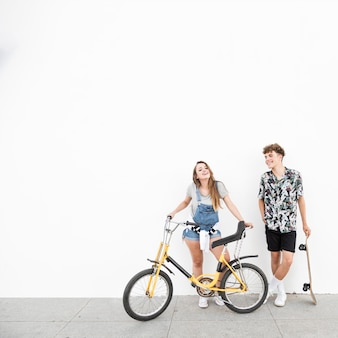 Smiling young couple with bicycle and skateboard against wall