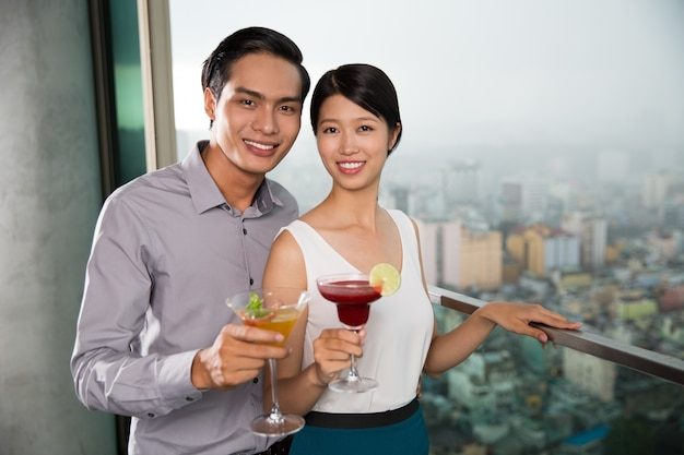 Smiling young couple with cocktails on balcony