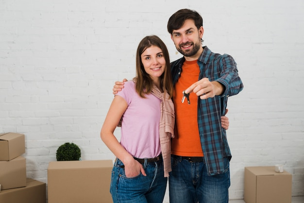 Smiling young couple with house keys in their new house