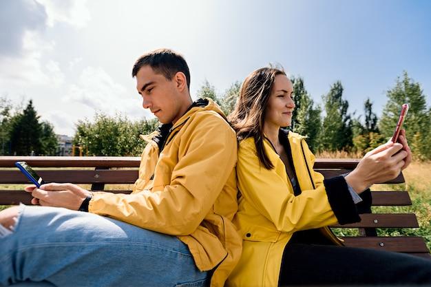 電話、スマートフォンを使用してベンチに座っている若いカップルの笑顔。ミレニアル世代、ガジェット、デバイスから切り離せない